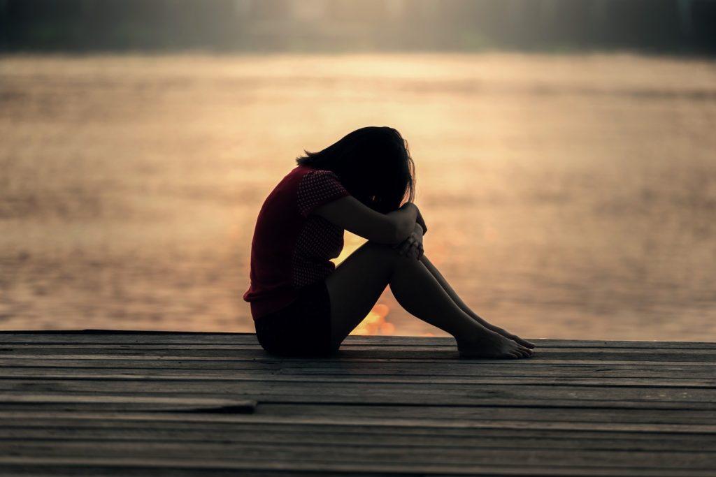 Depressie en burn-out. Foto van een jonge vrouw op een steiger.