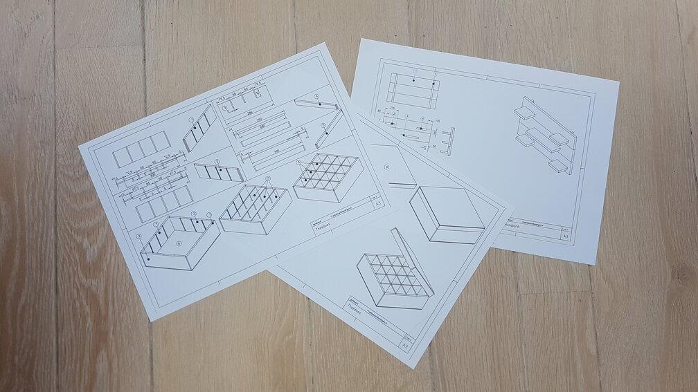 Foto van bouwtekeningen van een wandbord en een theedoos.