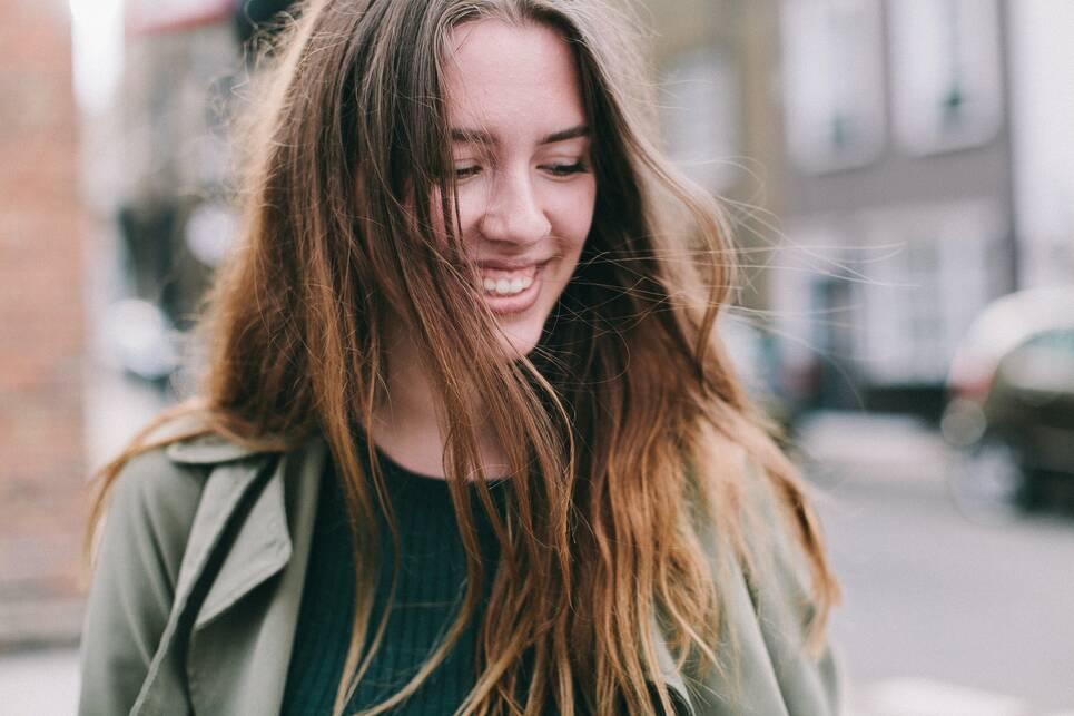 Foto van een lachende jonge vrouw op straat.
