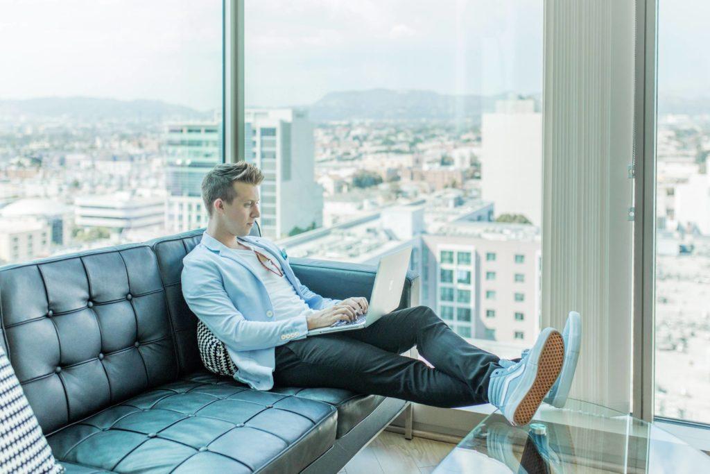 Foto van een jongeman die met een laptop op de bank zit