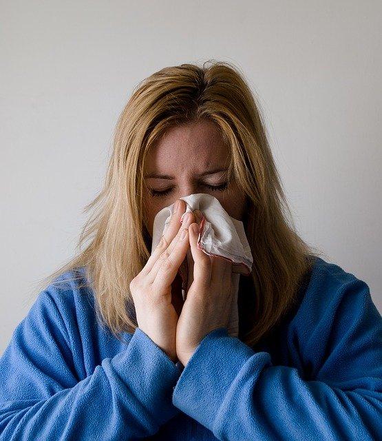 Foto van een verkouden vrouw die haar neus snuit
