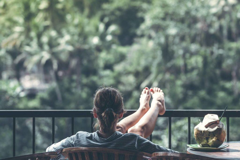 Tijd voor mindfulness. Foto van vrouw in een luie stoel op een balkon