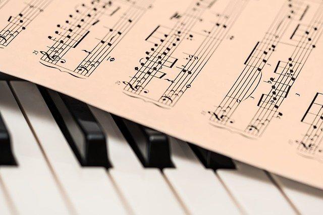 Foto van pianoklavier met bladmuziek.