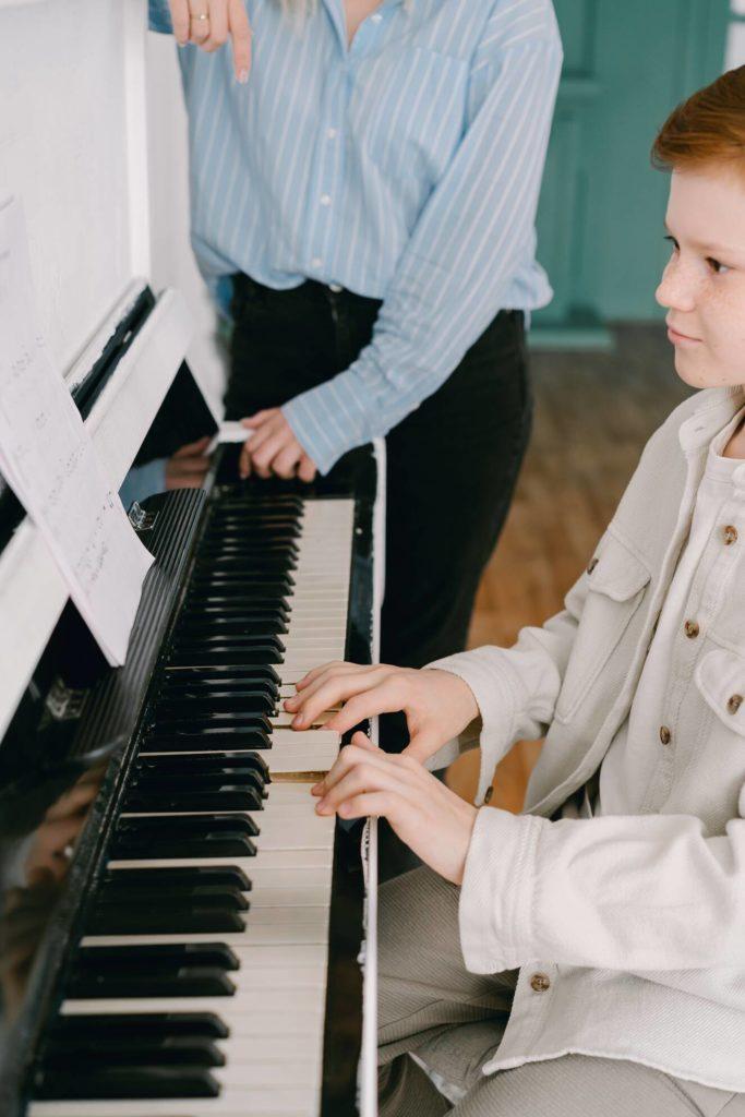 Foto van piano spelende jongen met piano lerares