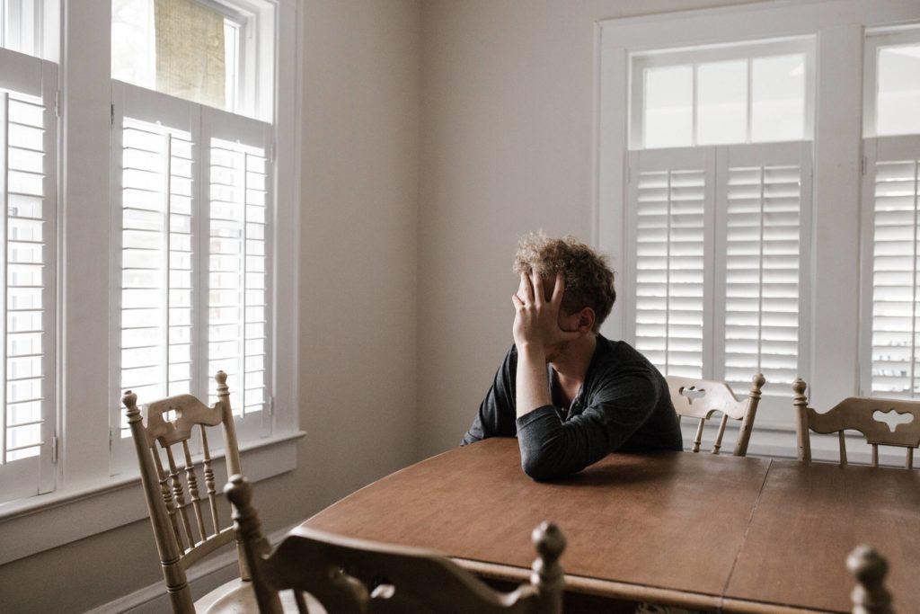 Depressie en burn-out. Foto van man aan tafel die zich zorgen maakt.