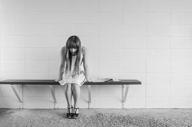 Foto van teneergeslagen meisje op bankje.