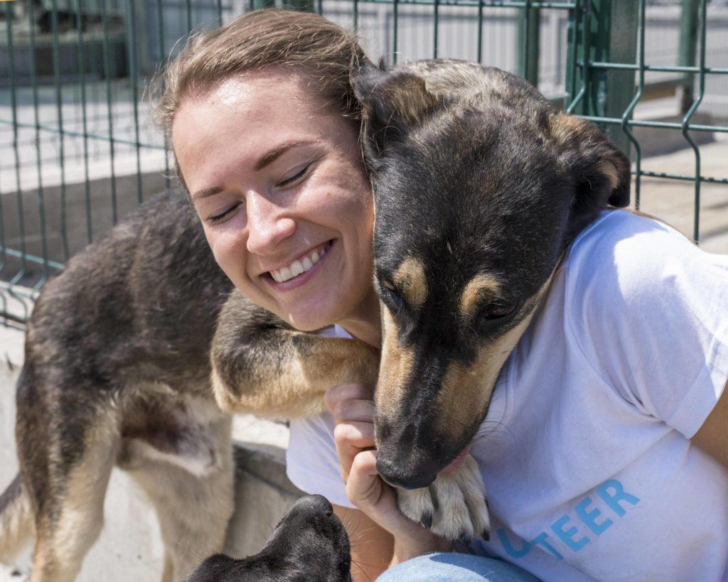 Foto van een een jonge vrouw en een hond die erg op elkaar gesteld zijn.